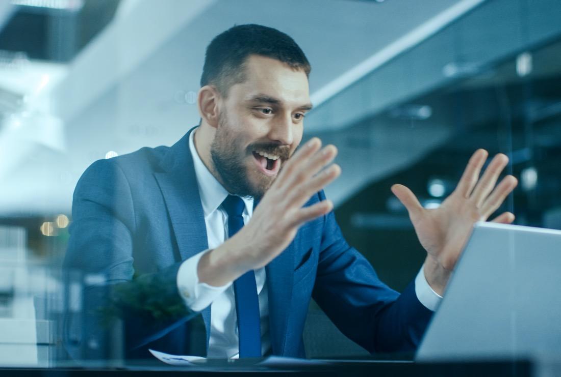 Mann am Laptop freut sich über Einladung zum Vorstellungsgspraech