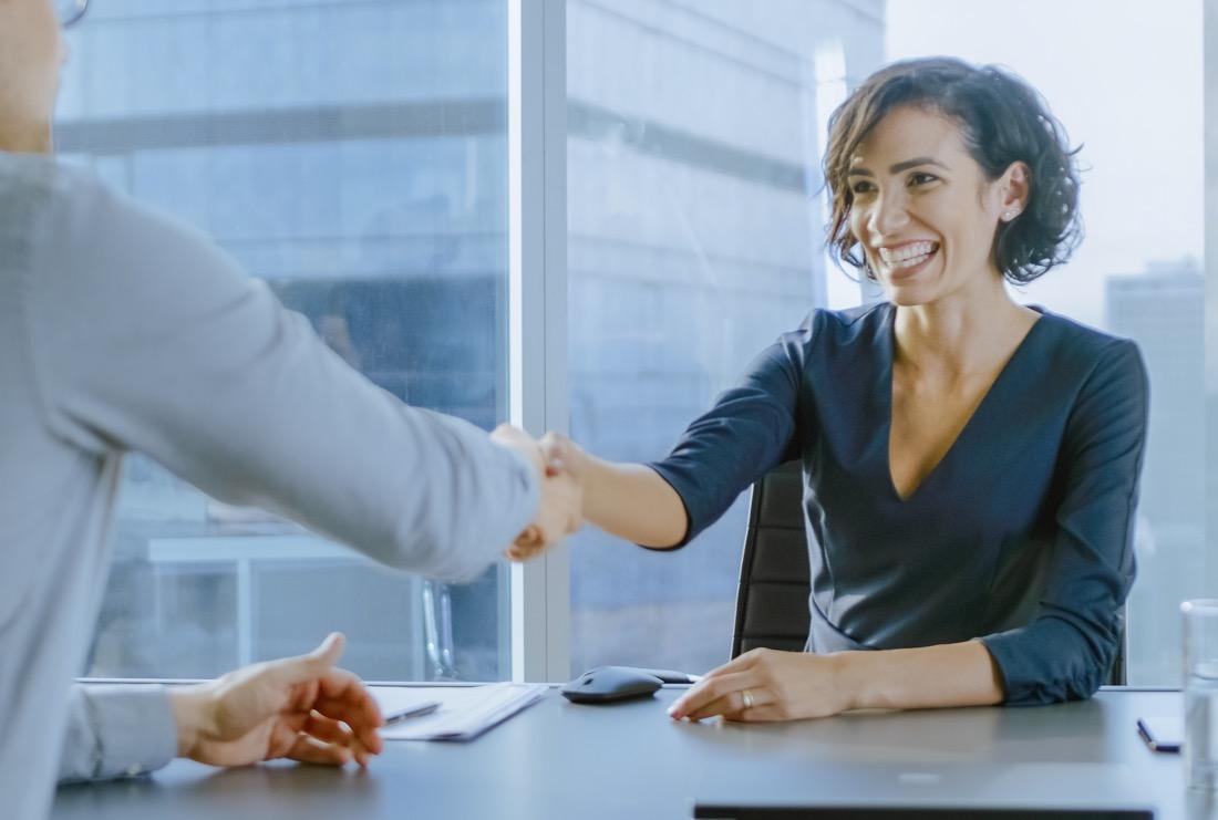 Vorstellungsgespräch: Frau reicht die Hand über Schreibtisch